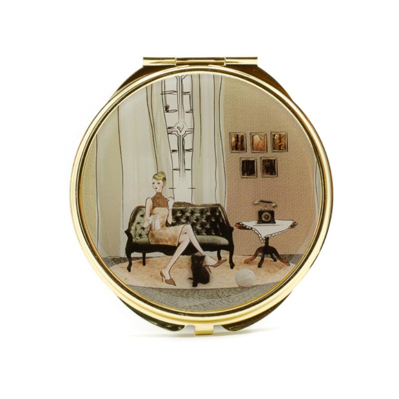 Kanapén ülő elegáns nő arany keretes zsebtükrön