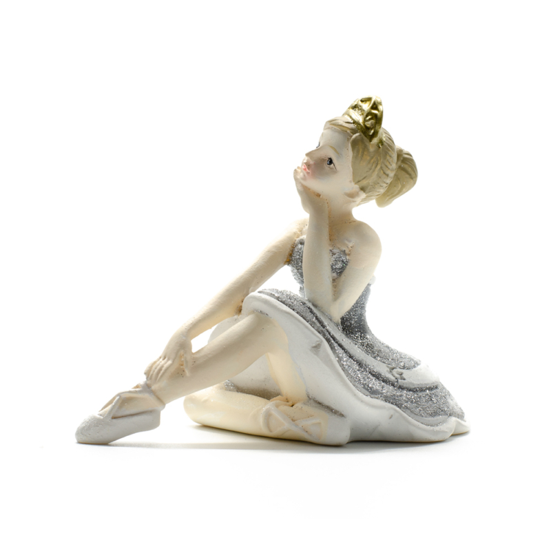 Ezüst csillogó tütüben kecsesen ülő és álát tartó balerina