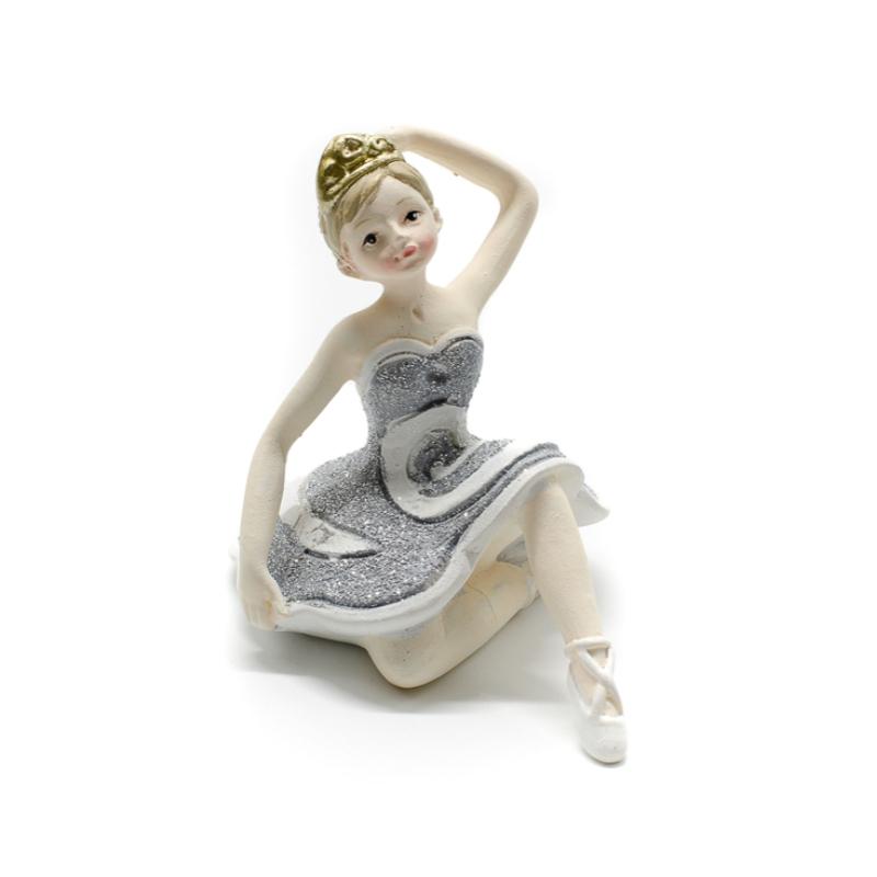 Ezüst csillogó tütüben kecsesen ülő és fejét érintő balerina