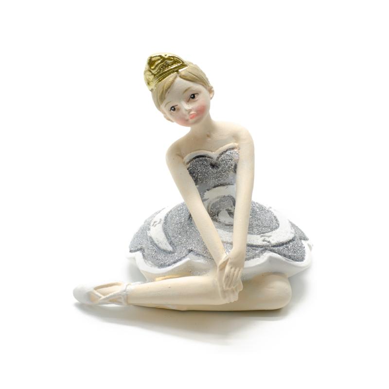 Ezüst csillogó tütüben kecsesen ülő és a térdét megérintő balerina