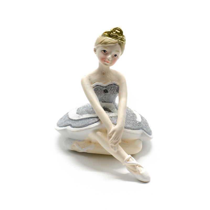 Ezüst csillogó tütüben kecsesen ülő és előre nyúló balerina